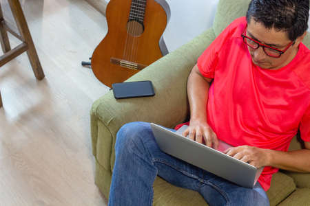 Shot of a man working in an armchair at home with his computer with the cell phone aside and a guitar behind him