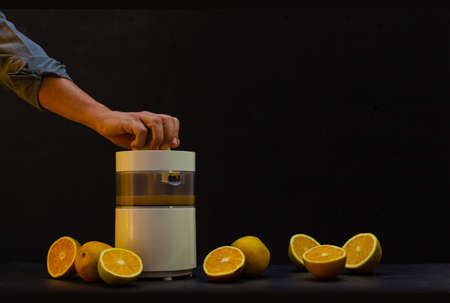 Shot of a hand squeezing oranges in a machine to prepare orange juice with black background and more split oranges around