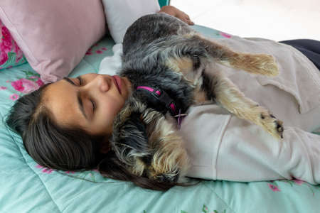 Girl and a dog embraced sleeping on the bedroom bed with a lot of relaxation