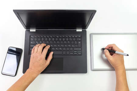 Man hands working with a computer and a graphics tablet with a cell phone aside isolated on white background