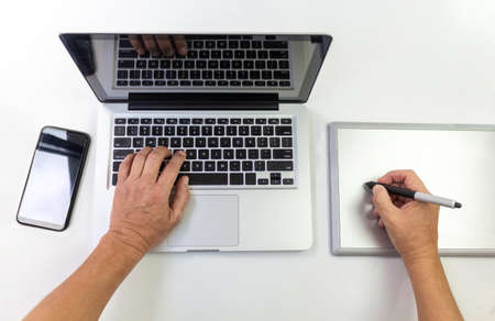 Aerial shot of hands working with a laptop and a graphics tablet with a cell phone aside on a white table Foto de archivo
