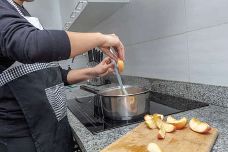 Hands cooking caramelized apples in a pot on an induction cooker. Process for preparing an apple cake
