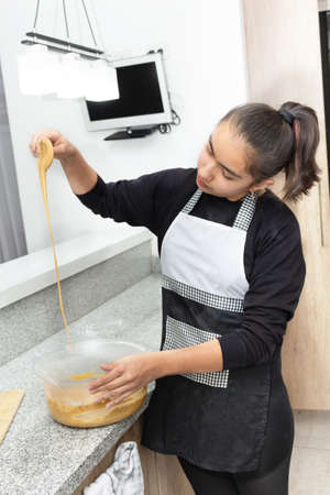 Girl to teenager mixing the dough for a cake. The dough falls from a spoon. Process for making apple pie 免版税图像