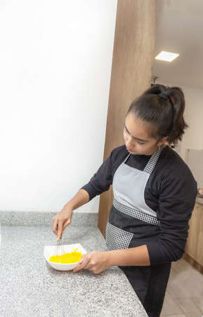 Teenage girl beating eggs in her kitchen to prepare a paste or omelet recipe 免版税图像