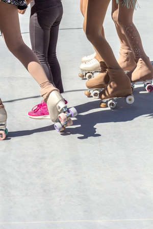 Close-up of legs of girls skating next to a girl in shoes. Figure skaters on wheels Stockfoto