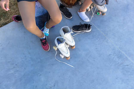 Top View of girls putting on roller skates for figure skating practice. Skater's legs