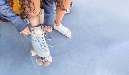 Top view of a girl tying her laces on her skates at a skating rink Stockfoto