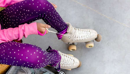 Legs of a skater who ties the laces of her roller skates. She's in a figure skating gloss suit