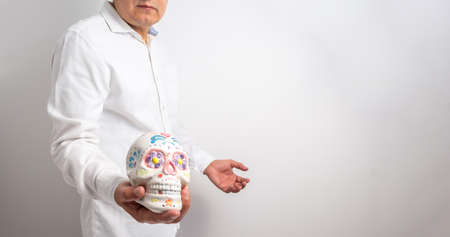 Isolated man on a white background shows a skull painted on the day of the dead or halloween. Selective focus