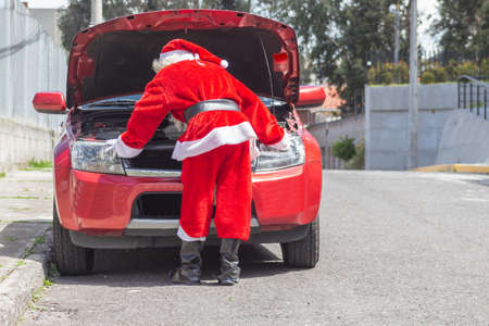 Santa Claus checking his car engine in front of his car that is damaged on Christmas. Man disguised on the street Stock Photo
