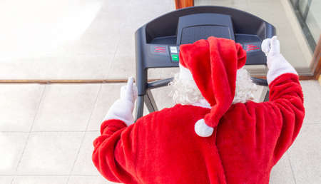 Santa Claus running on a treadmill in a gym at Christmas, shot from the back where you can see the white hair and the hat Stock fotó