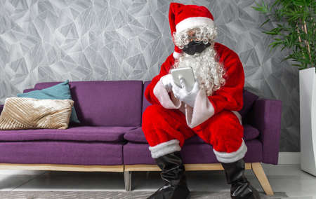 Santa Claus whit mask at Christmas using technology with a tablet sitting on a couch