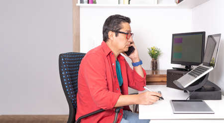 Freelancer man working from home on his computer with external monitor and graphic tablet talking on cell phone. Latin man designer