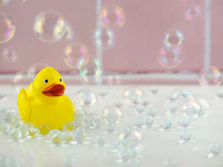 Yellow rubber duck in bathroom with bubbles and pink tiles Stock fotó