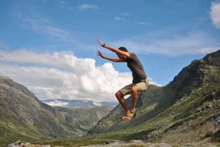 Young man jumping in the mountain air to express liberty and passion of sport photo