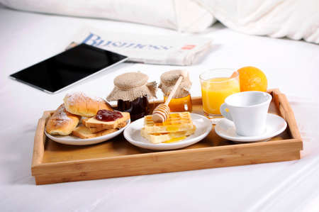 breakfast food: Breakfast tray laying on  bed in an hotel room