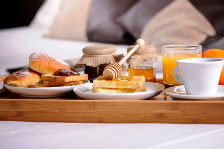 luxery: Breakfast tray laying on  bed in an hotel room