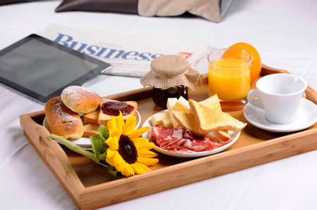 Breakfast tray laying on  bed in an hotel room photo