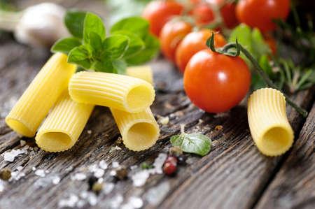 Raw rigatoni pasta with herbs