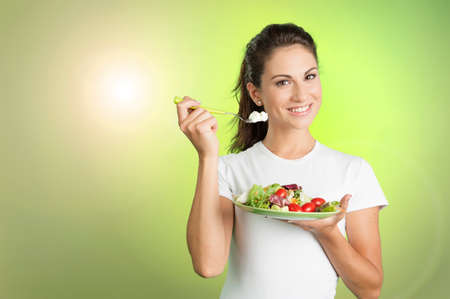 woman eating a salad on green background