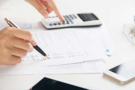 calculations: woman doing calculations on a calculator Stock Photo