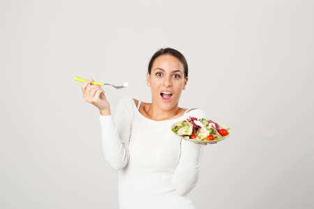 woman eating salad against a white background