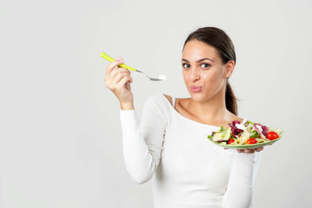 eating up: Young woman stand up eating a salad