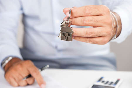 buying a house: Estate agent giving house keys on a silver house shaped keychain Stock Photo