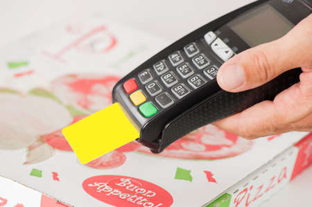 fast service: Take away Pizza payment with credit card through terminal Stock Photo