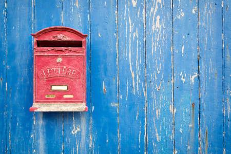 buz�n: Caja roja en la puerta de madera azul Foto de archivo