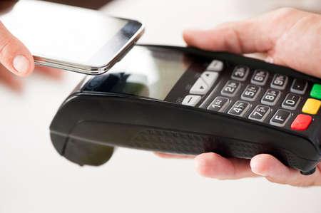 pagando: - NFC - pago móvil Near Field Communication Foto de archivo