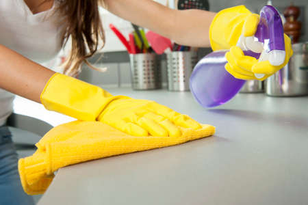Woman cleaning the counter in the kitchen Stock Photo