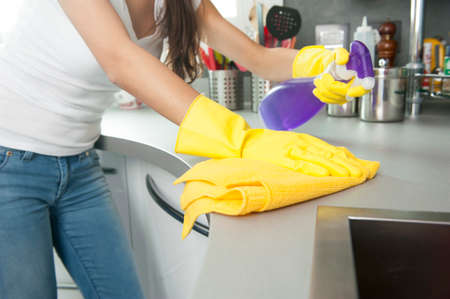 out of context: Woman cleaning the counter in the kitchen Stock Photo