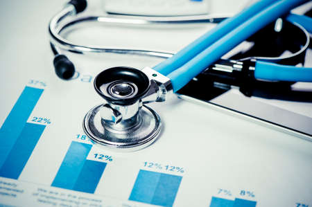 economy: Stethoscope and financial charts