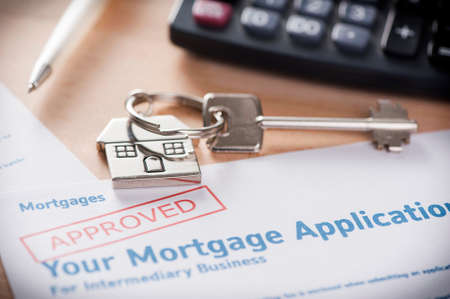 Approved Mortgage loan application with house key