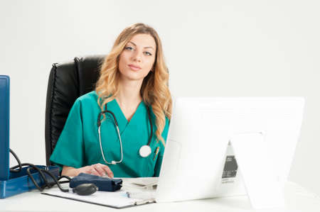 at her desk: Attractive female doctor sitting on her desk