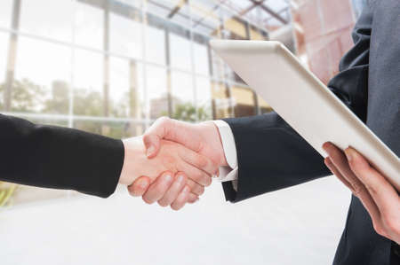 pact: Successful business people handshaking closing a deal