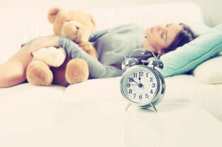 notecase: Alarm clock on table and woman laying on sofa
