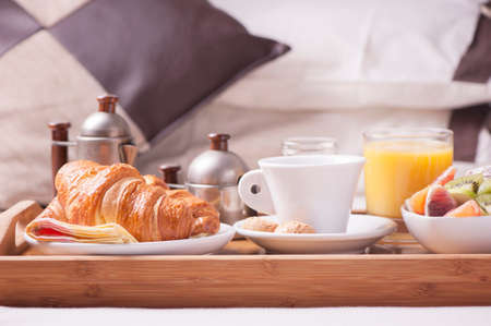 luxury bed: Breakfast in bed. Tray with coffee, croissants and fruits