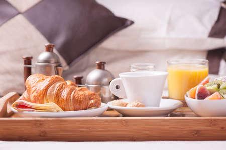 Frühstück im Bett. Tablett mit Kaffee, Croissants und Obst