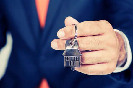 real man: Estate agent giving house keys on a silver house shaped keychain Stock Photo