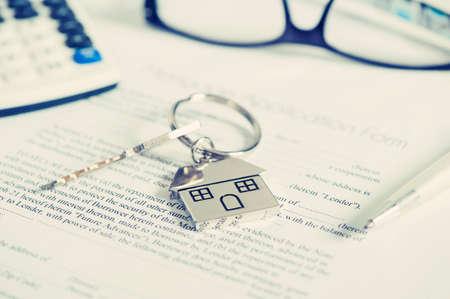 legal document: acuerdo aplicaci�n pr�stamo hipotecario con forma de casa llavero Foto de archivo