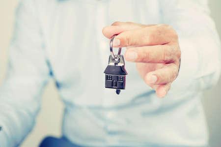 keys isolated: businessman holding a house key