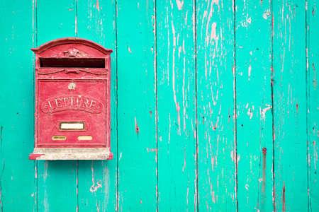 Red mailbox on the green wooden door