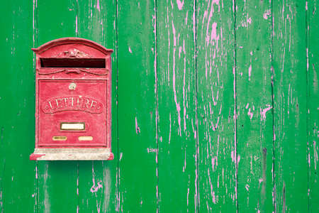 mailbox: Red mailbox on the green wooden door