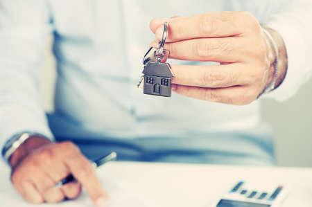 businessman holding a house key