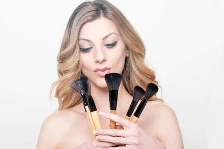 make up brushes: Beauty portrait of a woman holding make up brushes