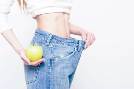 oversize: Young slim woman holding an apple and wearing oversize jeans on white