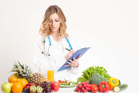 dietology: nutritionist writing medical records with fresh fruit and vegetables on foreground