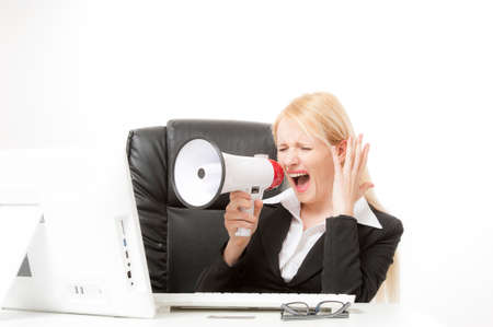 strict: business concept - strict businesswoman shouting in megaphone in office